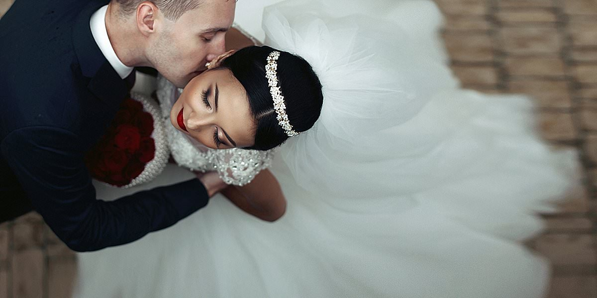 Romantic groom kissing brunette bride on the neck, shot from above closeup